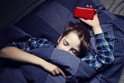 enfant garon au lit avec smartphone