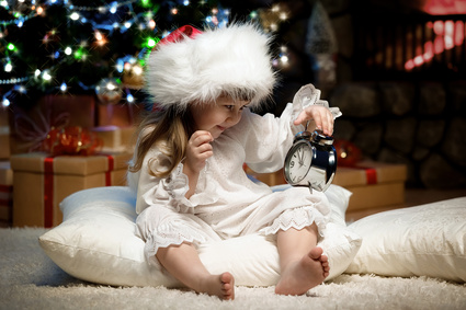 Portrait of girl with alarm clock under the Christmas tree